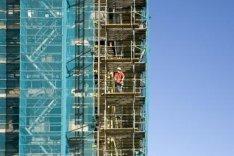 Oranje-Vrijstaatkade. Een bouwvakker op de bouwsteiger van het nieuwe Stadsdeelh…