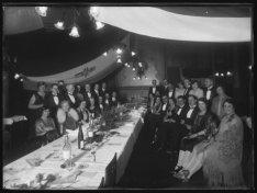Groepsfoto in een grote feestzaal met geschilderde wanddecoraties in het America…