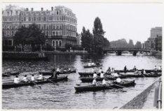 Amstel met wherries in het water. Amstel Hotel. Links achterzijde van het Amstel…