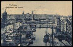 Damrak met diverse binnenvaartschepen en dekschuiten. Op de achtergrond het Cent…