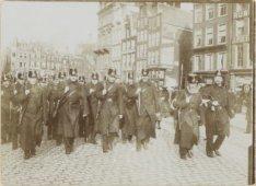 Militairen op het Koningsplein gezien naar de ingang van de Heiligeweg (links) e…