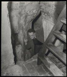 Een man wringt zich door de nauwe doorgang onder de koepel van de Ronde Lutherse…