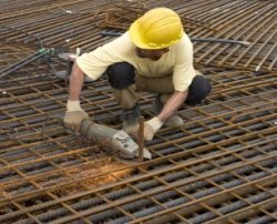 Het wegslijpen van overtollig betonstaal op de bouwplaats busterminal De Ruijter…