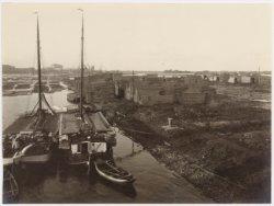 Houthaven met houtopslag, vlotten en 2 zwaarbeladen binnenvaartschepen