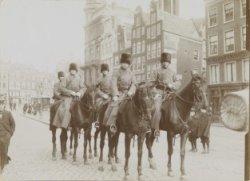 Zes militairen te paard op het Koningsplein, op de achtergrond het Singel
