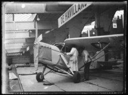Een vliegtuig met daarboven een bord met het opschrift: 'De Havilland'