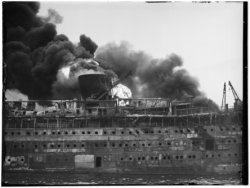 Het passagiersschip de Pieter Corneliszoon Hooft (P.C. Hooft) in brand op het Af…