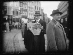 Een man leest op straat op het Muntplein het weekblad De Zondagavond