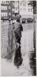 Een fietser in de regen op de Nieuwezijds Voorburgwal