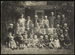 Groepsfoto van leerlingen, helpsters en onderwijzeres in de tuin van Christelijk…
