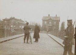 Politieagent en militair bewaken de brug over de Oosterdoksdoorgang