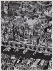 Luchtfoto van het Damrak (onderaan) en omgeving gezien in westelijke richting