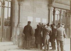 Amsterdammers lezen een plakaat op de voorgevel van het Centraal Station, Statio…