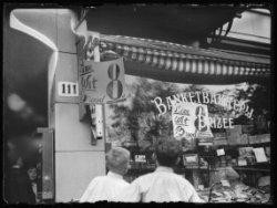 Etalage van bakkerij Brizée, Mauritskade 111, met reclame voor goedkoop witbrood…