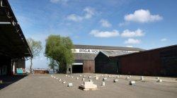 Houtloodsen op het terrein van RIGA Houtconstructies, Gevleweg 10. Op de achterg…
