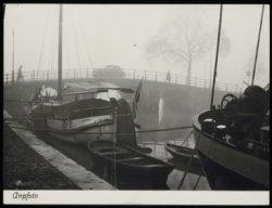 Woonschepen liggen aan wal in de mist, Keizersgracht bij de Amstel