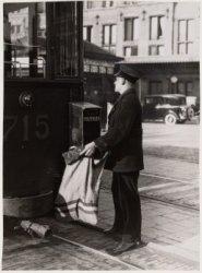 Stationsplein. Het ledigen van een brievenbus aan een tram (bijwagen 715)