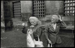 Dam, twee dames met regenkapjes voor het Koninklijk Paleis