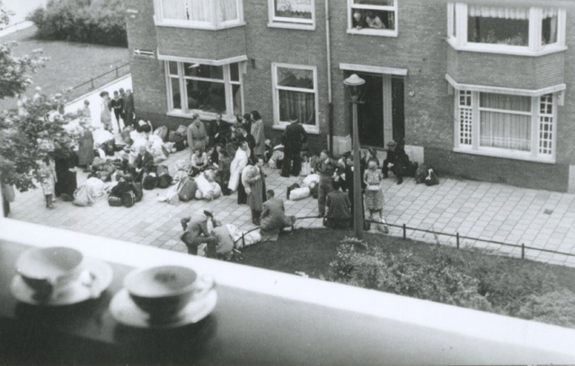 A photo taken through a window with two teacups in the foreground, showing a group of people and their bags on a street outside