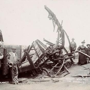 Groepsfoto bij kromgebogen spoorrails ten gevolge van een dynamiet ontploffing