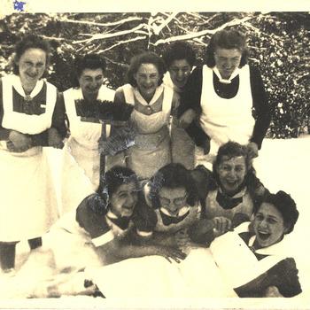 Foto ziekenverpleegsters in de besneeuwde tuin van het Apeldoornsche Bosch, Apeldoorn