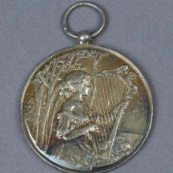 verguld zilveren medaille, onderdeel van vaandel  apeldoorns mannenkoor, 12 augustus 1906.