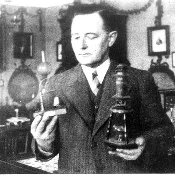 Concierge Blom met wekkertje in voormalige Oudheidkamer voor Tiel en Omstreken, circa 1935