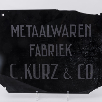 Naambord van glas van de fabriek van Kurz, 1984