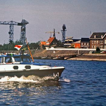 Kleurenfoto van een douaneboot met op de achtergrond het douanekantoor van Tolkamer door Piet Zwemstra 1985