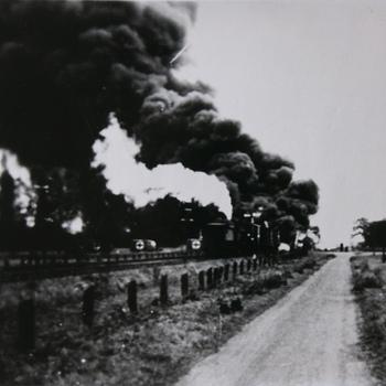 een in brand geschoten Duitse olietrein ergens tussen Duiven en Westervoort. De uitgebrande trein werd later teruggesleept naar het toenmalige station in Westervoort.  WOII.