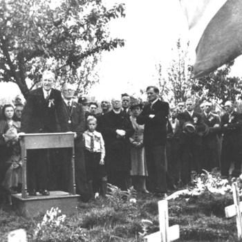 Herdenking bij de graven van gesneuvelde geallieerde militairen. Op het spreekgestoelte pastoor Kamerbeek, daarachter burgemeester Wiessing (met ambtsketen). Naast de burgemeester de familie Siebenheller, waarvan 'n zoon en broer gesneuveld was op de Grebbeberg.  WOII,