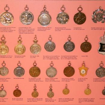 Vitrinekast van plexieglas (roze achtergrond) met daarin medailles van zilver gewonnen door leden van schuttergilde EMM Lobith