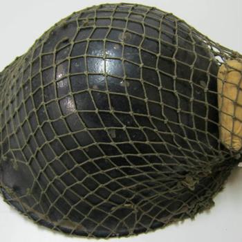 Helm van metaal met binnenhouder, inclusief camouflagenet en pakje verband, behorend bij militair uniform gedragen door Canadezen