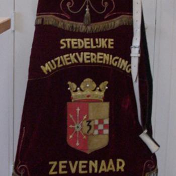 Vaandel van textiel met stok, standaard van metaal en vaangordel van leer van de Stedelijke Muziekvereniging Zevenaar ca. 1976