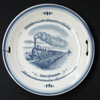 Jubileumbord van steengoed Delftsblauw met een afbeelding van een rijdende stoomtrein door Zenith 1939