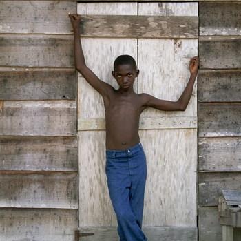 Jongen met blauwe spijkerbroek voor schuur