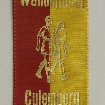 Vaantje van gele en rode kunstzijde met goudkleurige bedrukking.