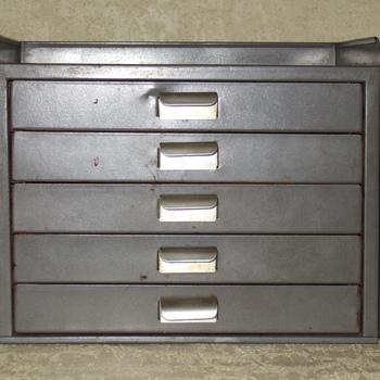 Kastje van grijs gelakt metaal van het merk Gispen, voor o.a. het opbergen van postzegels.