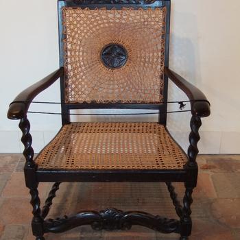 Stoel van houten frame met zitting van gevlochten rotan.