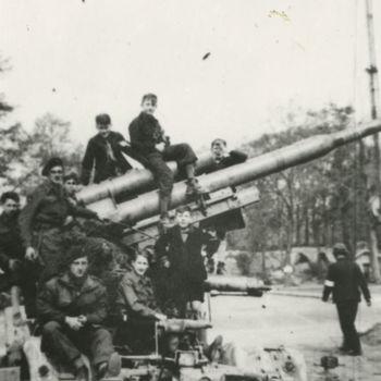 Foto uitgeschakeld Duits 88mm kanon met Britse militairen en jongens er op. Wellicht Nijmegen, Keizer Lodewijkplein.