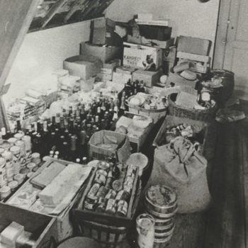 Foto van zolder met flessen en manden en dozen met blikken