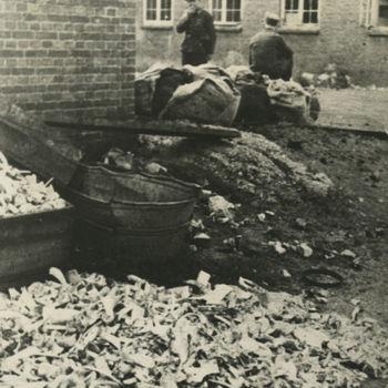 Foto van aardappelschillen en emmer bij hoek gebouw