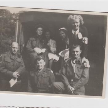 Enkele medewerksters van het Rode Kruis, vergezeld door militairen