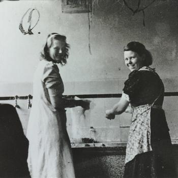 twee jonge vrouwen staan te wassen bij een aanrecht