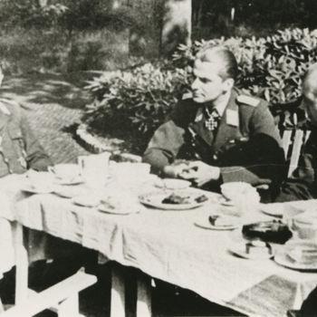 Foto van drie Duitse Luftwaffe officieren om tafel in tuin. Tekst: geen.
