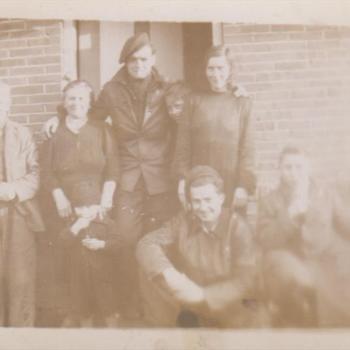 Foto van twee Canadese Militairen met twee vrouwen, een jongen en twee mannen voor een huis