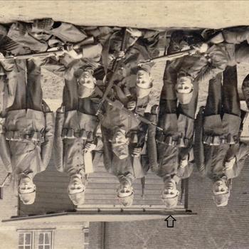 Foto van een 13 Nederlandse soldaten voor een houten barak en stenen bebouwing