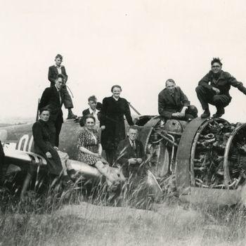 Foto van een militair en 11 burgers (zes mannen en vijf vrouwen) op wrak Amerikaans P-47 Thunderbolt jachtvliegtuig. Tekst achterop: geen.