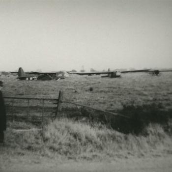 """Foto van weiland met gelande Waco CG-4A zweefvliegtuigen. Links staat een burger voor een hek. Tekst achterop: """"Waco Overasselt""""."""