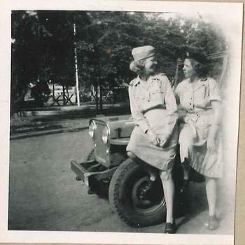Twee leden Vrouwenkorps KNIL op de motorkap van een auto in Nederlands-Indië
